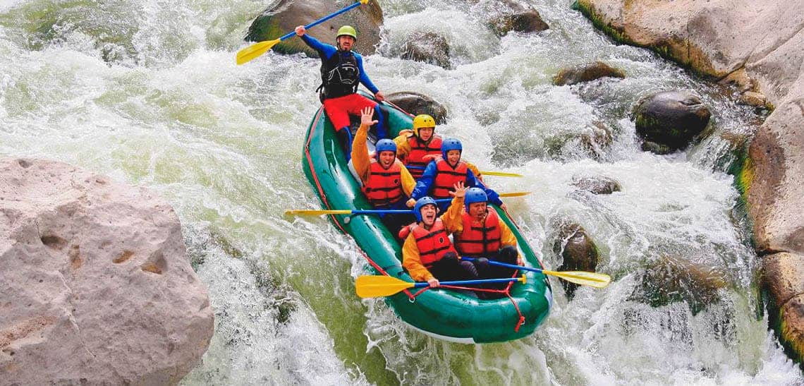 5 tourists dressed in life-jackets and helmets and an instructor flowing through rapids on a river.